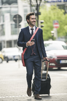 Smiling businessman walking in the city with cell phone and suitcase - UUF17684