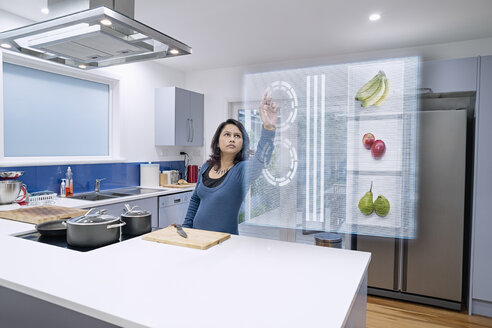 Mixed race woman using holographic screen in kitchen - BLEF03959