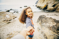 Girl pulling hand of mother on beach - BLEF03962