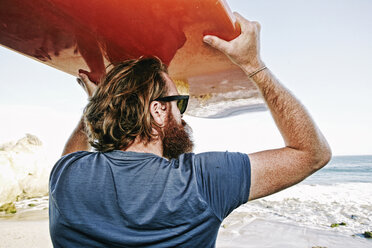 Caucasian man holding surfboard at beach - BLEF04034