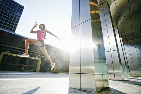 Black woman running and jumping on city sidewalk - BLEF04196