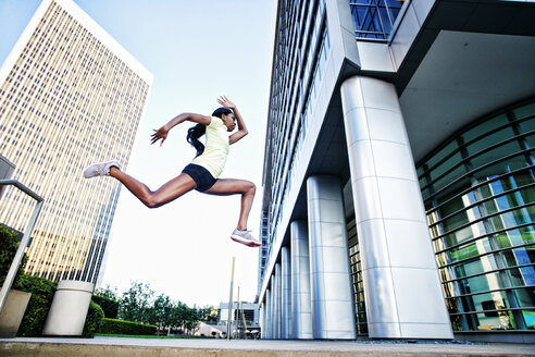 Black woman running and jumping on city sidewalk - BLEF04199