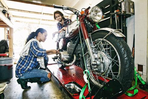 Man watching woman repairing motorcycle in garage - BLEF04214
