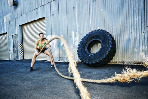 Mixed Race woman working out with heavy ropes outdoors - BLEF04256