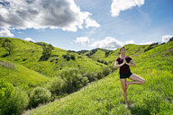 Caucasian woman doing yoga on hill - BLEF04289