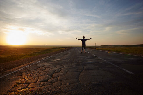 Caucasian man standing in cracked road at sunset with arms outstretched - BLEF04328