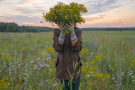 Caucasian woman holding bouquet of flowers over face in field at sunset - BLEF04343