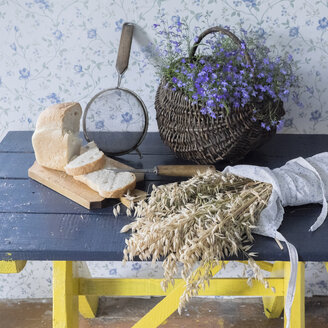 Wheat, sliced bread, sieve and flowers on bench - BLEF04382