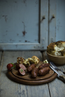 Fried salsiccia on cutting board with pickled bread - MAEF12875