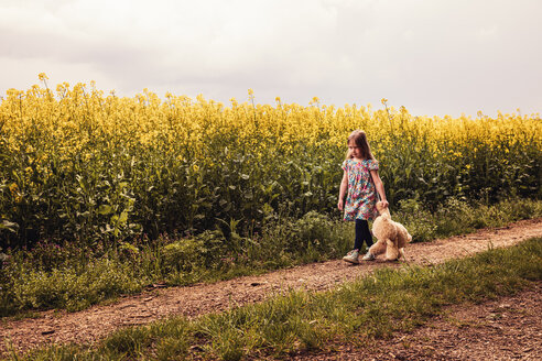 Girl walking alone with teddy and backpack on a field way - SEBF00102