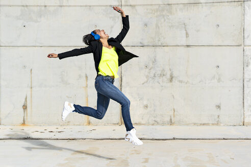 Woman with blue headphones listening music, jumping in the air and taking a selfie - ERRF01366