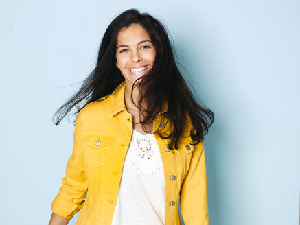 Portrait of young woman with black hair wearing yellow denim jacket, light blue background - HMEF00398