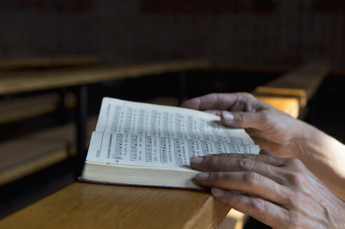 Hands on hymnbook on pew - ASF06430