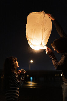 Father and daughter preparing a sky lantern at night - ERRF01379