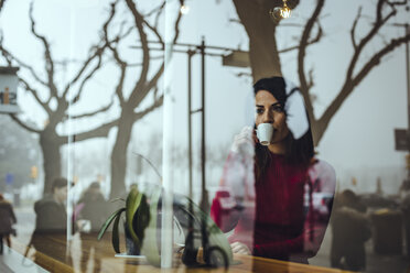 Young woman drinking cup of coffee behind windowpane in a cafe - ACPF00512
