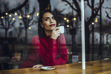 Young woman with cup of coffee behind windowpane in a cafe - ACPF00515