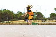 Teenage girl jumping on basketball ground - ERRF01382