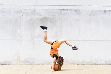 Teenage girl doing acrobatics with basketball outdoors - ERRF01388