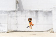 Teenage girl jumping with basketball outdoors - ERRF01391