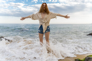 Redheaded young woman standing at seafront with arms outstretched - AFVF02982