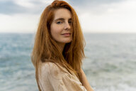 Portrait of redheaded young woman with nose piercing standing in front of the sea - AFVF02985