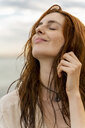 Portrait of happy redheaded young woman with nose piercing in front of the sea by sunset - AFVF02991