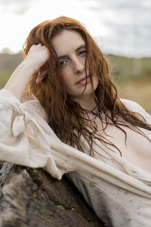 Portrait of redheaded young woman with nose piercing leaning against rock - AFVF02994