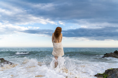 Back view of redheaded shirtless young woman standing in front of the sea - AFVF03003