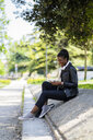 Smiling woman resting in urban park using cell phone - GIOF06349