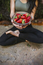 Close-up of woman in yoga pose holding bowl with strawberries - LJF00009