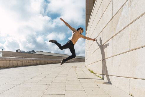 Young man doing acrobatics at a wall outdoors - AFVF03019