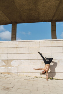 Young man doing a handstand at a wall outdoors - AFVF03022