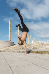 Young man doing acrobatics on stairs outdoors - AFVF03025