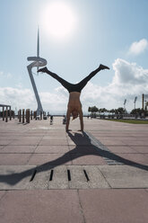 Young man doing a handstand in backlight - AFVF03028