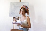 Portrait of young female painter in art studio next to empty canvas - JPTF00060