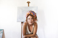Portrait of young female painter in art studio next to empty canvas - JPTF00063
