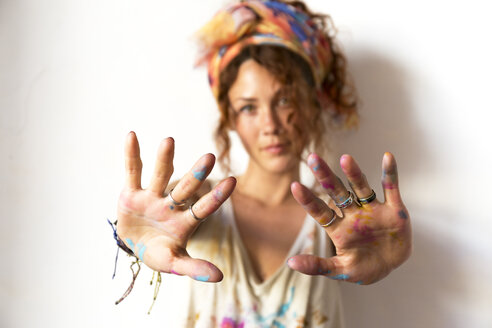 Portrait of young artist in her studio showing her painted hands - JPTF00069