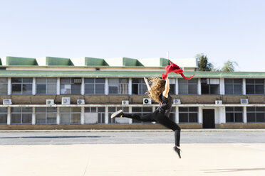 Teenage girl jumping outdoors with red cloth - ERRF01399