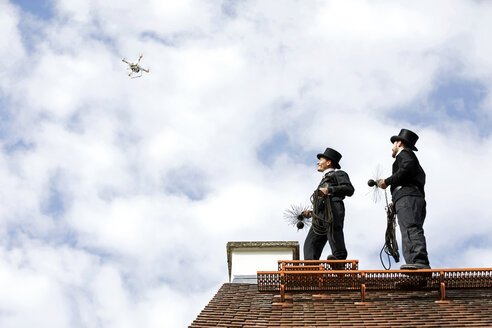 Two chimney sweeps on house roof looking at drone - MAEF12891