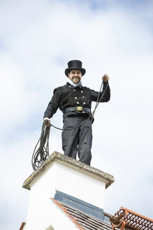 Portrait of smiling chimney sweep working on house roof - MAEF12894