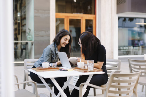 Two friends sitting together at a pavement cafe with book and laptop - OCAF00383