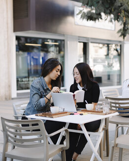 Two friends sitting together at a pavement cafe with book and laptop - OCAF00386