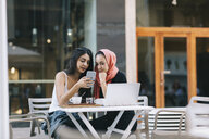 Two friends sitting together at a pavement cafe using cell phone - OCAF00404