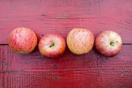 Close up of row of red apples on red wooden table - BLEF04443