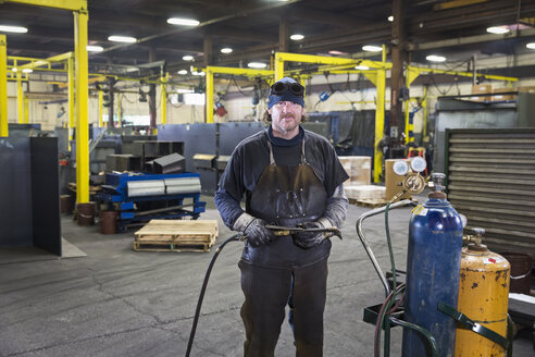 Caucasian welder posing with blowtorch in factory - BLEF04470