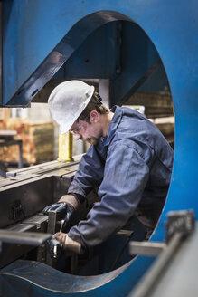 Caucasian worker fabricating metal in factory - BLEF04482