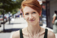 Caucasian woman with nose ring smiling on city sidewalk - BLEF04512