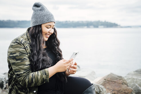 Smiling Mixed Race woman texting on cell phone near ocean - BLEF04581