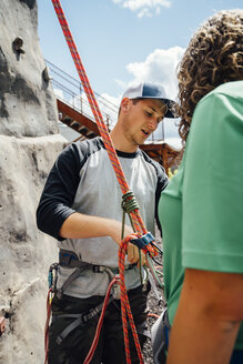 Caucasian man fastening rope to harness at rock climbing wall - BLEF04584