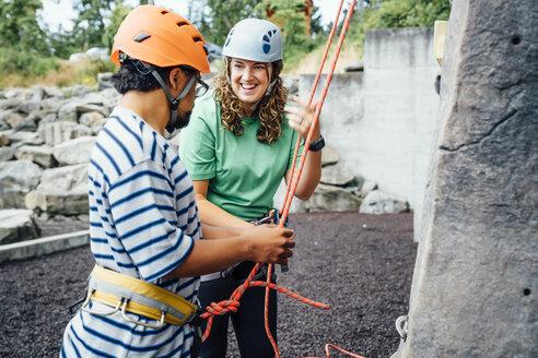 Woman smiling to man preparing to climb rock climbing wall - BLEF04587